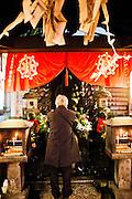 Praying at Buddha image at Hozenji Temple, Dotonburi/Minami area.