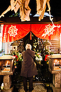 Praying at Buddha image at Hozenji Temple, Dotonburi/Minami area.
