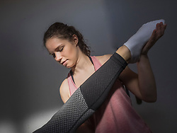 Fitness instructor helping young woman doing physical therapy in athletics hall, Offenburg, Baden-Wuerttemberg, Germany