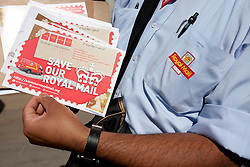 © Licensed to London News Pictures. 10/07/2013. London, UK. A Royal Mail employee holds a campaign leaflet as postal workers and campaigners from the Communication Workers Union protest outside the Royal Mail headquarters against privatisation of Royal Mail in London today (10/07/2013). Photo credit: Matt Cetti-Roberts/LNP