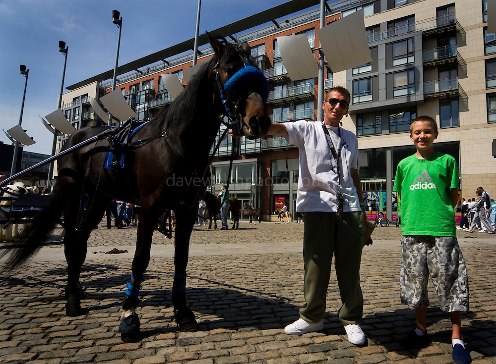 Editorial Use only....L-R, Geronimo, James and Jamie at Smithfield Horse Market, Dublin. I got talking this man and his son, and the asked me to take their picture with their mount, Geronimo....The horse market at Smithfield, Dublin takes place on the first Sunday of every month. People come from all over Ireland to trade horses and equipment. It's absolute chaos, with young kids galloping across the cobbles on distressed looking ponies, horses whinnying, gardai chasing jaunting cars on their bicycles. A big part of the horse scene involves the keeping of animals, by Dublin urban youth, in gardens or public areas. The Dublin Society for Prevention of Cruelty to Animals says that the market facilitates the sale of horses to under-16s, who are then unable - or unwilling to look after them. Amongst the dozens of horses visible, I did see a couple of examples of cruelty - the most obvious one of all was by an elderly man, kicking his pony in the stomach for no apparent reason. ....There's talks by Dublin City Council of moving the market out of the city - as Smithfield becomes increasingly gentrified, the more urbane of the urban dwellers in the surrounding apartments are apparently unimpresssed with the smell of horse shit once a month!....Editorial Use only