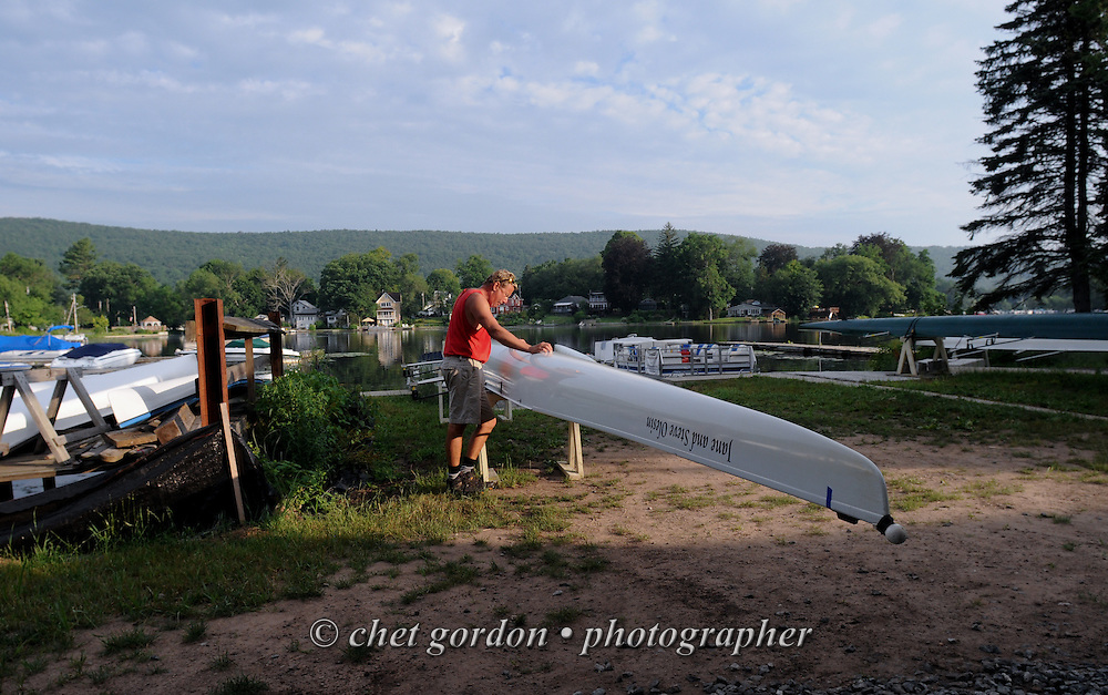 A man pauses near a four-man boat after a morning row in Greenwood Lake, NY on Tuesday, July 9, 2013.