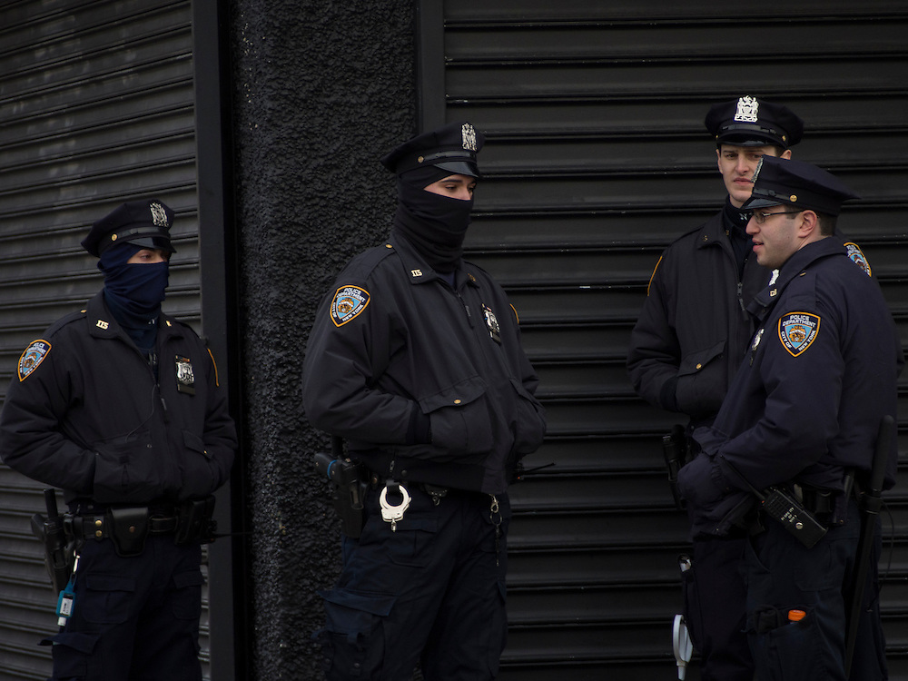 Police officers stand on a street corner block away from a memorial for Kimani Gray at E 55 St and Church Ave in Brooklyn, NY on Sunday, March 17, 2013...Photograph by Andrew Hinderaker