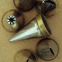 Collection of tin and brass cake icing nozzles standing and lying on antique paper