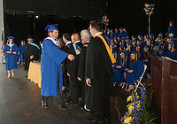 """Jonathan Lou """"Jack"""" Athanas is congratulated on stage after receiving his diploma from Principal Peter Sawyer during Gilford High School's commencement exercises Saturday morning at Bank of NH Pavilion at Meadowbrook.  (Karen Bobotas/for the Laconia Daily Sun)"""