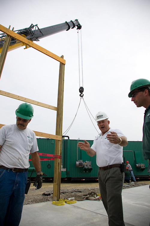 Anthony Pennington, left, Mick Harris, center, and Bill Lawless, right, coordinate before a crane lowers the Wright Environmental in-vessel composting unit that is being installed at the Ohio University compost site on Dairy Lane. Photo By: Josh Armstrong