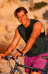 good looking All American man outdoors with a bicycle at sunset