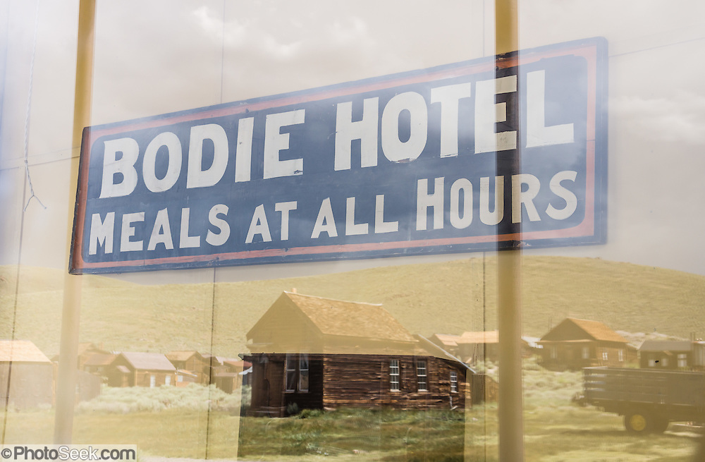 """Bodie ghost town buildings reflect in a window fronting the Wheaton and Hollis Hotel. A sign visible indoors reads """"Bodie Hotel -- Meals at all Hours"""". In 1885-86, this building served as the United States Land Office. Later, it was the office for the Power Company, then the Bodie Store, and finally the Hotel. Bodie is California's official state gold rush ghost town. Bodie State Historic Park lies in the Bodie Hills east of the Sierra Nevada mountain range in Mono County, near Bridgeport, California, USA. After W. S. Bodey's original gold discovery in 1859, profitable gold ore discoveries in 1876 and 1878 transformed """"Bodie"""" from an isolated mining camp to a Wild West boomtown. By 1879, Bodie had a population of 5000-7000 people with 2000 buildings. At its peak, 65 saloons lined Main Street, which was a mile long. Bodie declined rapidly 1912-1917 and the last mine closed in 1942. Bodie became a National Historic Landmark in 1961 and Bodie State Historic Park in 1962."""