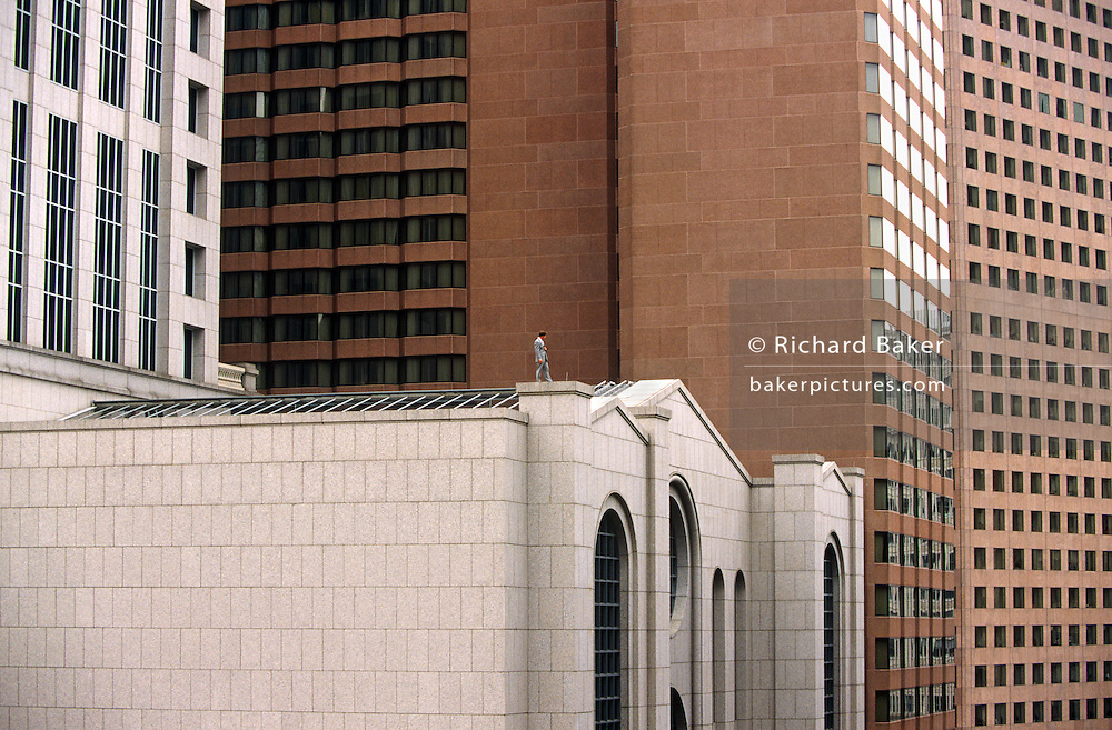The solitary figure of a man stands on the roof of an office building in downtown Atlanta during a victory parade for the city's baseball team. The man may be a security guard, keeping watch over the streets below as crowds gather to honour the Atlanta Braves Baseball team, after their 1995 World Series win. The figure is in his manmade environment and the high walls and windows of the buildings that make up this metropolis dwarf this tiny human who in the scale and perspective of a modern city looks incongruous, isolated and insignificant.