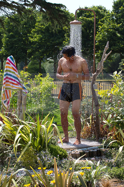 © Licensed to London News Pictures. 08/07/2013. London, UK. Garden Designer Bayley LuuTomes cools off in his award winning garden 'The Native Shower' at the press view for the Royal Horticultural Society's Hampton Court Palace Flower Show today (08/07/2013). Photo credit: Matt Cetti-Roberts/LNP