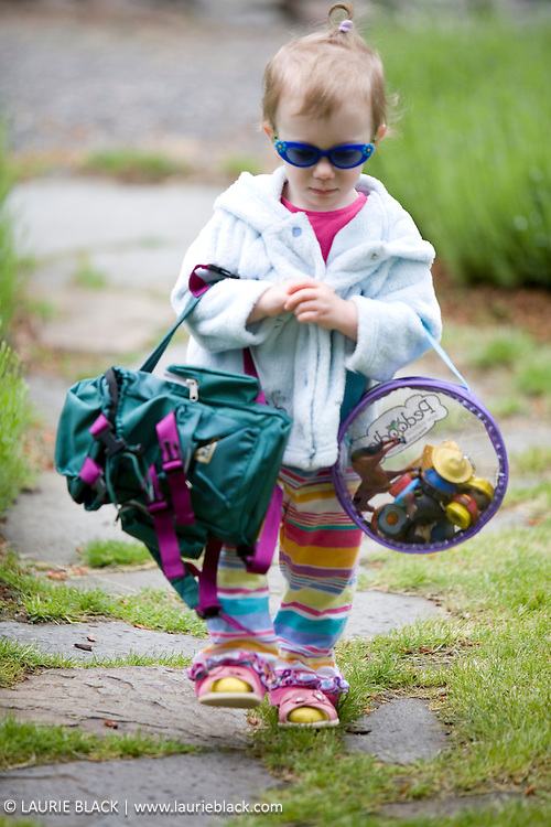 Girl todler with sunglasses and bags.