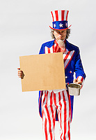 Uncle Sam on white background holding cardboard sign and a beggars cup...Model Release: 20080813_MR_A
