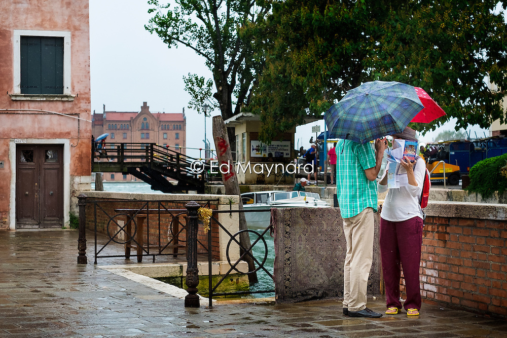 Tourists consult their map in the rain, Dosoduro, Venice, Italy.<br />