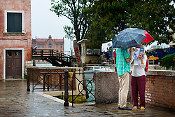 Tourists consult their map in the rain, Dosoduro, Venice, Italy.<br /> Photo: Ed Maynard<br /> 07976 239803<br /> www.edmaynard.com