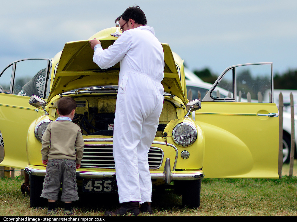© Licensed to London News Pictures. 16/09/2012. Goodwood, UK . A young boy looks into the bonnet of a car. People enjoy the atmosphere at the 2012 Goodwood Revival. The event recreates the glorious days of motor racing and participants are encouraged to dress in period dress. Photo credit : Stephen Simpson/LNP