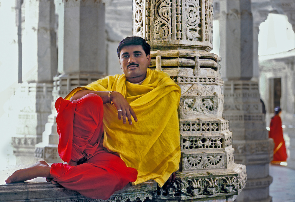 Gentleman on retreat at the 15th century Jain Temple to Adinath at Ranakpur pauses willingly for a portrait.  Within the precinct no shoes and no leather (such as in belts or watch bands) is permitted.  The gentleman wears bright red pants and a bright yellow shawl.