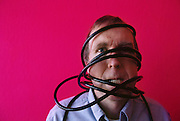 Wired magazine. Executive editor, Kevin Kelley in office entry area, wrapped in cables. Model Released. (1996).