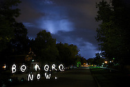 """be here now"" written with flash light at night"