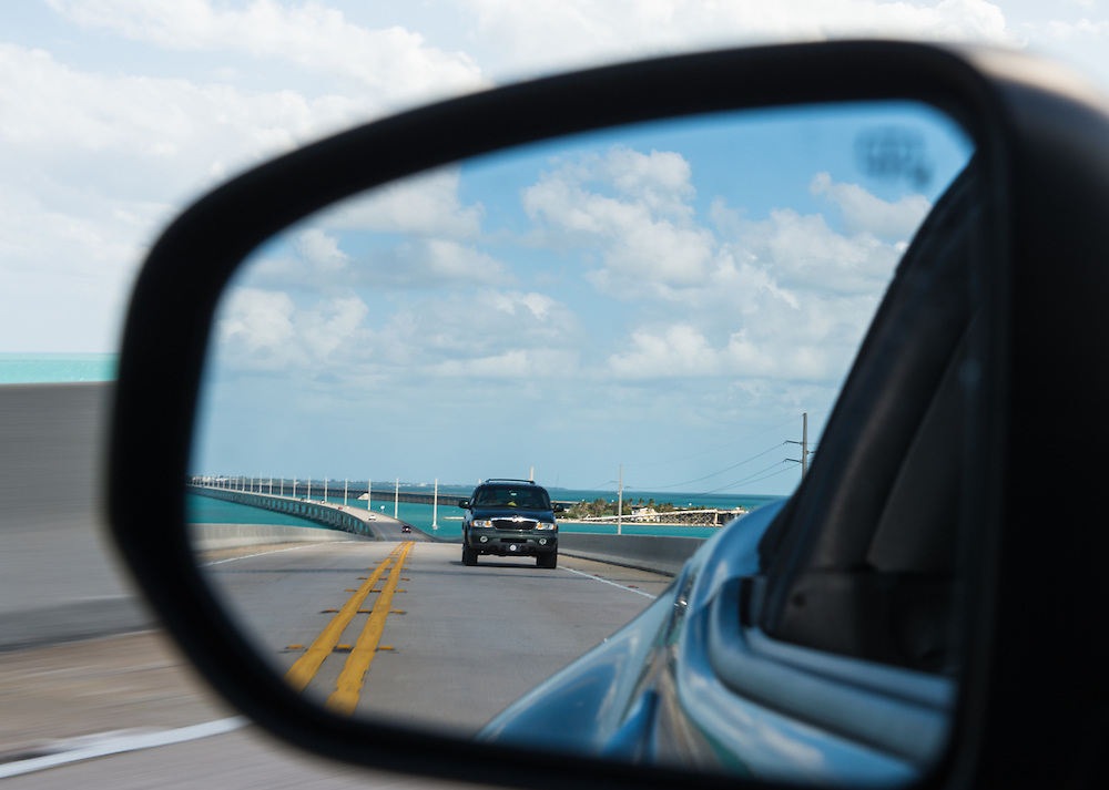 Famous Seven Mile Bridge reflected in car rear mirror crossing the bridge