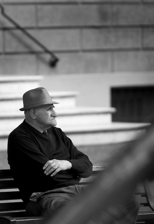 Black and white photography.Man with hat sitting on a bench in Bologna Italy.