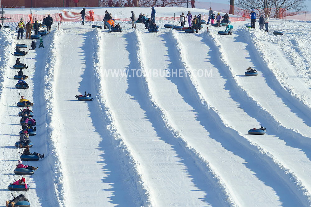 Hamptonburgh, New York - People slide down the snow tubing hill while other, at left, ride the tow rope to the top, at Thomas Bull Memorial Park on Jan. 6, 2013.