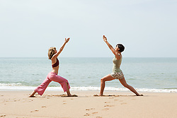 Jul. 25, 2012 - Two women practicing yoga on a beach (Credit Image: © Image Source/ZUMAPRESS.com)