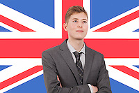 Young businessman with arms crossed over British flag