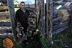 The worker of a private farm carries cut off antlers of a deer to the high temperature drying room in the Altai (eastern Siberia) village of Mendur-Sokon, Russia, 24 July 2001. Local population traditionally sell pants (the young, just grown antlers of a deer) to farmacilogical factories, which produce extremely effective biological active medicine Pantacrin with high tonic effect. The antlers are sold by local people for about $150 per kilo, which cost up to $500 on Asian markets..