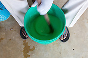 Jovita Masanyika's husband stirring the shampoo she is making in a bucket.<br /> <br /> Jovita set up and now runs a soap making business selling a variety of soaps from shampoo to disinfectant.<br /> <br /> She attended MKUBWA enterprise training run by the Tanzania Gatsby Trust in partnership with The Cherie Blair Foundation for Women.