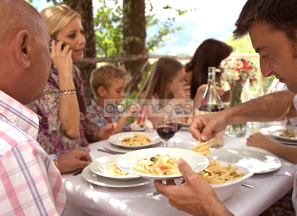 Extended family sitting at table having pasta meal