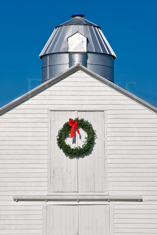 A well kept white barn decorated with a Christmas wreath on a sunny day.