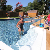 Gina Fremont gets ready to help Noah Massengill into her pool for his swimming lesson.