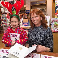 Grace Hoyne from Clarecastle getting a signed copy of Deefers Day Out by author Etain McCooey's at Ennis Book Shop
