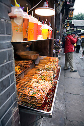 Numerous bits of skewered food, including squid, bugs, tofu, and mystery meat await the steaming wok in this tiny food stall in Ciqikou Old Town, Chongqing, China.