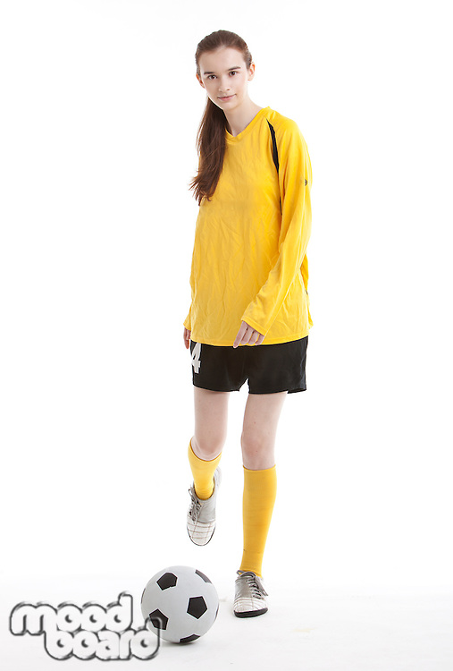 Portrait of young female soccer player kicking the ball against white background