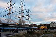 The Cutty Sark and nearby carousel at sunset, Greenwich, London, UK