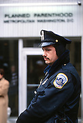 A Washington police officer stands guard at the Planned Parenthood clinic following threats during the annual Anti-Abortion protest January 22, 1997 in Washington, DC.