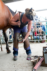 © Licensed to London News Pictures. 21/07/2015. Llanelwedd, UK. Farriers compete in the Open Traditional Hunter Shoeing competition on the second day of the show. The Royal Welsh Show is hailed as the largest & most prestigious event of it's kind in Europe. In excess of 200,000 visitors are expected this week over the four day show period - 2014 saw 237,694 visitors, 1,033 tradestands & a record 7,959 livestock exhibitors. The first ever show was at Aberystwyth in 1904 and attracted 442 livestock entries. Photo credit: Graham M. Lawrence/LNP