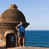 Smiling portrait of woman standing by turret of San Cristobal Castle, Old San Juan, Puerto Rico,