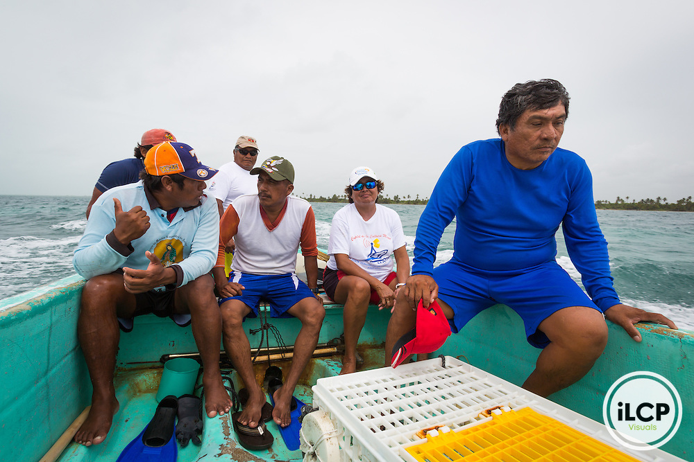 Hilario Salub (background center, driving boat) hosts conventional lobster fishermen from Progresso, Mexico, in La Victoria, a small, remote fishing camp in the Sian Ka'an Biosphere Reserve in southernmost Caribbean Mexico. Fishermen use 'casitas cubanas', small concrete hutches that provide shelter and attract lobsters to concentrated areas where they can be more sustainably and effectively harvested by hand. This helps avoid by-catch, taking berried females and juveniles, and unnecessary impact to the reef. By limiting the fisherman's range through free diving it also leaves a larger population of larger lobsters in deeper water that can 'resupply' the shallow water populations. Lobsters are held in live tanks and driven every few days out to the cites where buyers purchase them for regional distribution to hotels and restaurants in places like Cancun. From a 2014 iLCP (International League of Conservation Photographers) expedition project documenting the people and places of the Mexican section of the Mesoamerican Reef (MAR).