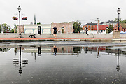 """Annapolis, Maryland - June 05, 2016: A woman walks her dog in front of a huge puddle in front of the Harbor Master's office on Dock Street in Historic Annapolis Sunday Morning June 5th, 2016. The puddle is an example of nuisance flooding and was exacerbated by the morning's perigean spring tide.<br /> <br /> <br /> A perigean spring tide brings nuisance flooding to Annapolis, Md. These phenomena -- colloquially know as a """"King Tides"""" -- happen three to four times a year and create the highest tides for coastal areas, except when storms aren't a factor. Annapolis is extremely susceptible to nuisance flooding anyway, but the amount of nuisance flooding has skyrocketed in the last ten years. Scientists point to climate change for this uptick. <br /> <br /> <br /> CREDIT: Matt Roth for The New York Times<br /> Assignment ID: 30191272A"""