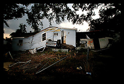 23 June, 2006. New Orleans, Louisiana. Upside down car. Lower 9th ward. Many months after hurricane Katrina, a Ford pick up truck remains pinned under a house in the Lower 9th ward.