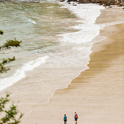 A couple hiking on a cloudy morning on Sand Beach in Maine's Acadia National Park.