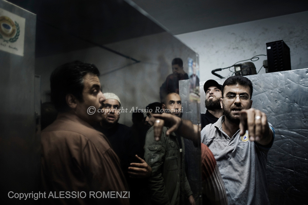 Gaza City: Palestinians mourners gesture in anger towards journalists covering the arrival at the Al Shifa Hospital morgue, of the body of Ramez Harb, an Islamic Jihad Militant killed by Israeli airstrike directed to the Al Shoroq building in Gaza city. November 19, 2012. ALESSIO ROMENZI