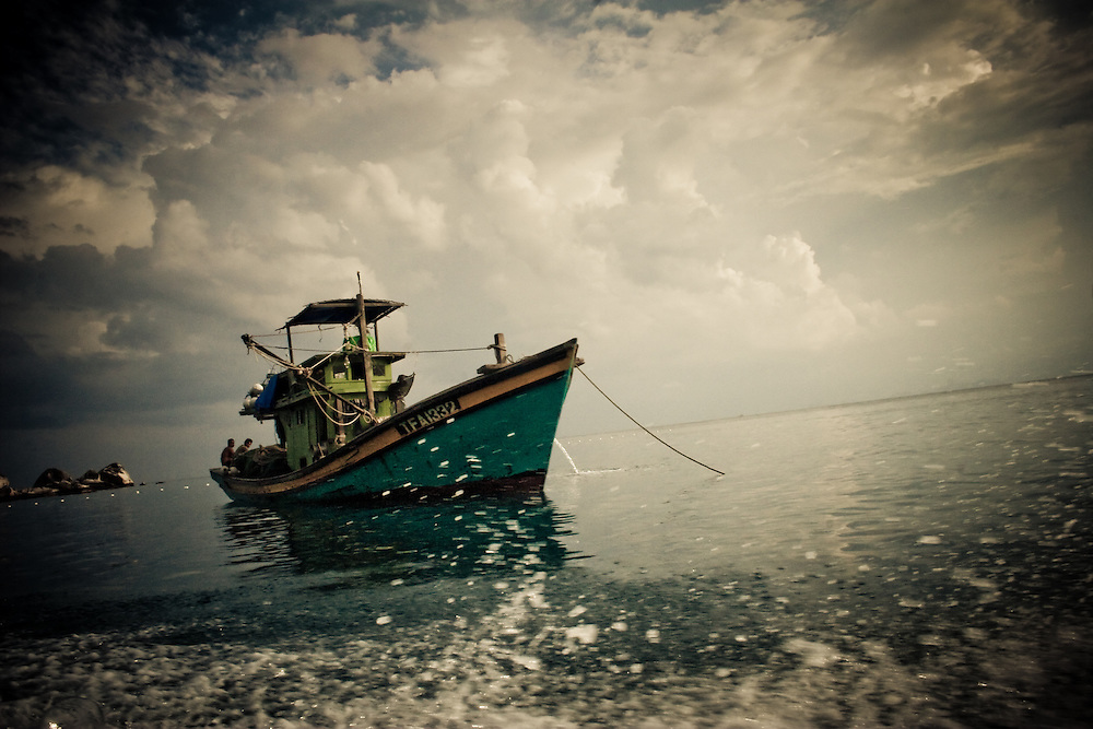 Fishermen rest on their boat near Pulau Perhentian Besar, Malaysia, Southeast Asia.
