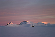 Evening light shines on mountains seen across the Greenland ice cap during a British mountaineering expedition to Knud Rasmussens Land, East Greenland, Arctic, 2006.