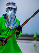 09 MARCH 2015 - NA KHOK, SAMUT SAKHON, THAILAND:  A worker on a salt farm, covered head to food to protect her from the sun, rakes salt in a pond in Samut Sakhon, Thailand. The coastal provinces of Samut Sakhon and Samut Songkhram, about 60 miles from Bangkok, are the center of Thailand's sea salt industry. Salt farmers harvest salt from the waters of the Gulf of Siam by flooding fields and then letting them dry through evaporation, leaving a crust of salt behind. Salt is harvested through dry season, usually February to April. The 2014 salt harvest went well into May because the dry season lasted longer than normal. Last year's harvest resulted in a surplus of salt, driving prices down. Some warehouses are still storing salt from last year. It's been very dry so far this year and the 2015 harvest is running ahead of last year's bumper crop. One salt farmer said prices are down about 15 percent from last year.   PHOTO BY JACK KURTZ