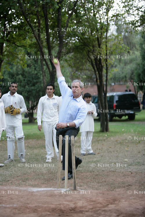 President Bush plays cricket at the US Embassy in Islamabad, Pakistan, Saturday, March 4, 2006. ..Photo by Khue Bui