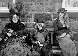 © Licensed to London News Pictures.01/11/15<br /> Whitby, UK. <br /> <br /> Three visitors to the Whitby Goth Weekend sit on a bench as they join hundreds of others at the event in Whitby, North Yorkshire. The event began in 1994 to celebrate goth culture and music and takes place twice each year. <br /> Thousands of extravagantly dressed people attend the popular event wearing Steampunk, Cybergoth, Romanticism, Victoriana and other clothing as they take part in the celebration of Goth culture. <br /> <br /> Note to Editors - Picture shot on Kodak Tri X 400ISO film.<br /> Photo credit : Ian Forsyth/LNP