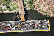 A barge ships flattened cars to New Orleans for shredding and sorting.